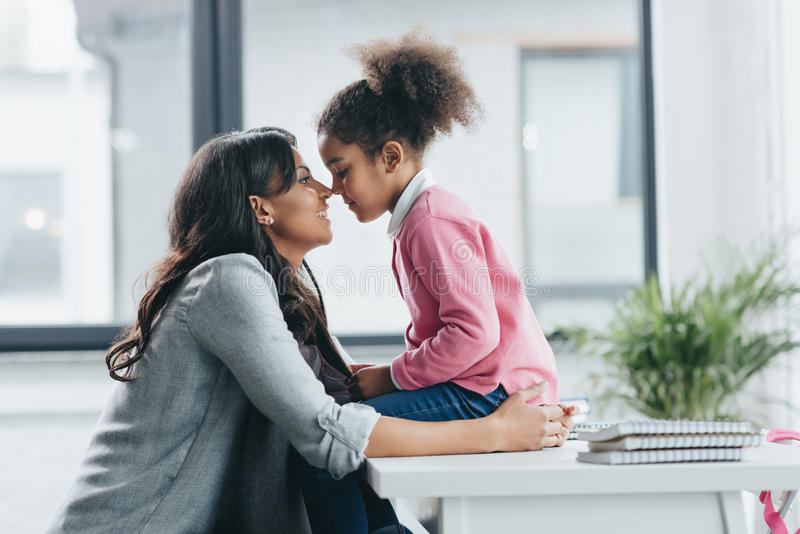 African american mother able to kiss her little daughter royalty free stock images