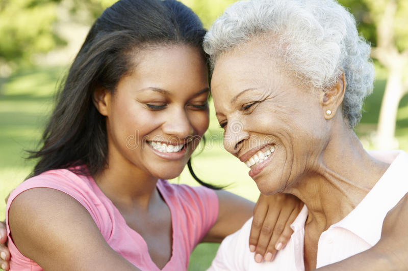 African American Mother And Adult Daughter Relaxing In Park stock image