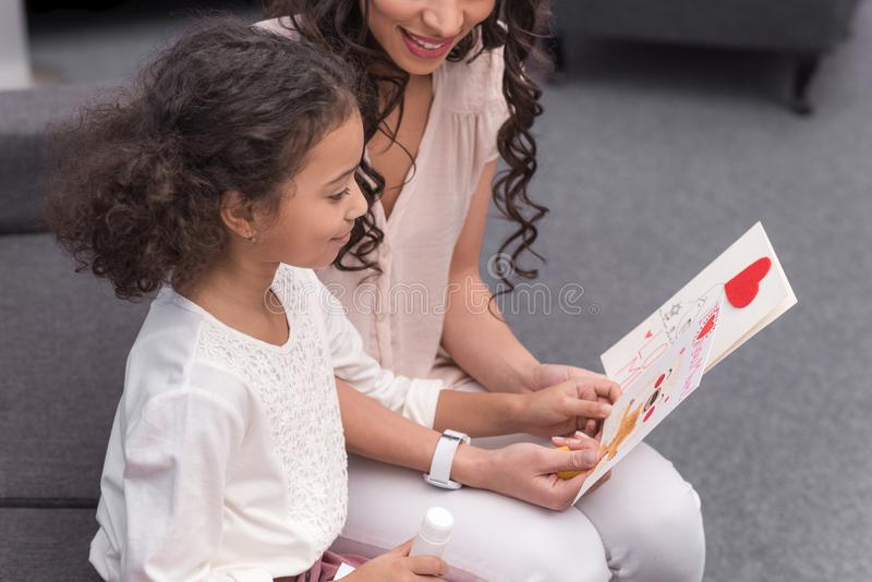 African american mother and daughter looking at greeting cards on mothers day at home stock photography
