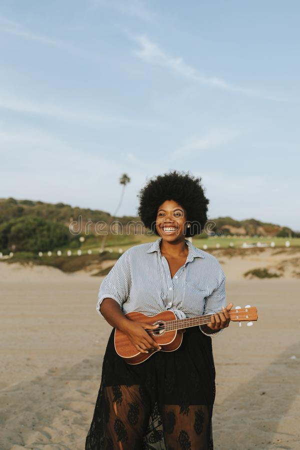 African American musician playing ukulele at the beach stock images