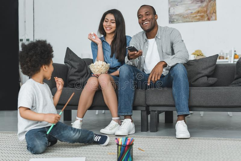 African american parents watching tv and son playing on floor. At home royalty free stock images