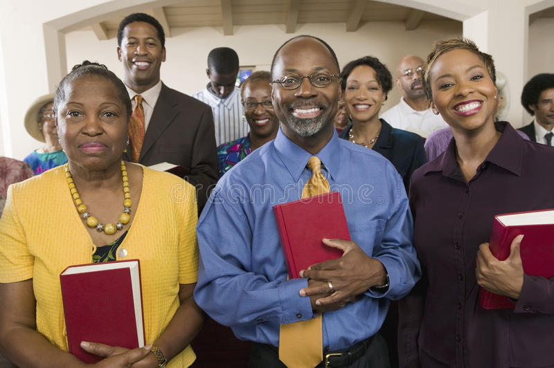 African American People With Bibles In Church. Portrait of smiling African American people standing with bibles in the church stock photos