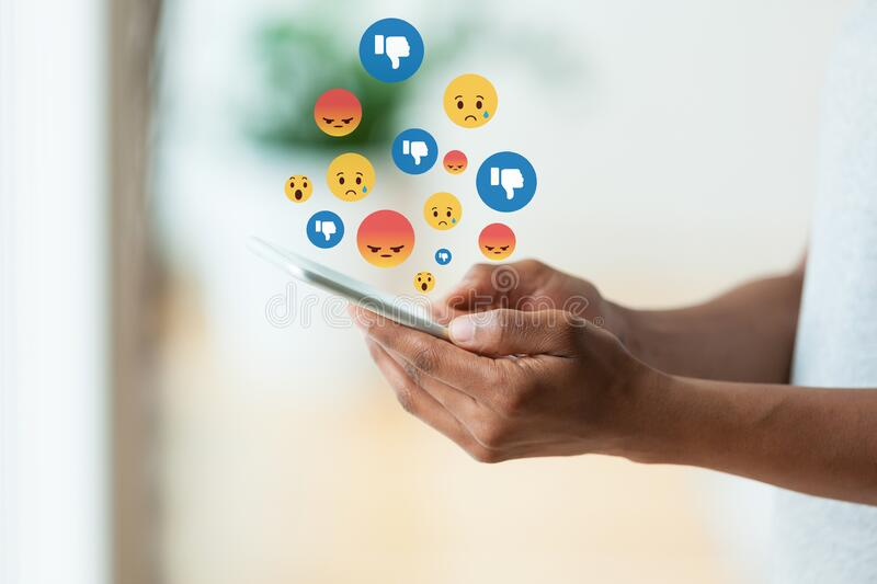 African american person holding a tactile mobile smartphone sending text messages emoji emoticon - Black people. African american person holding a tactile mobile stock images