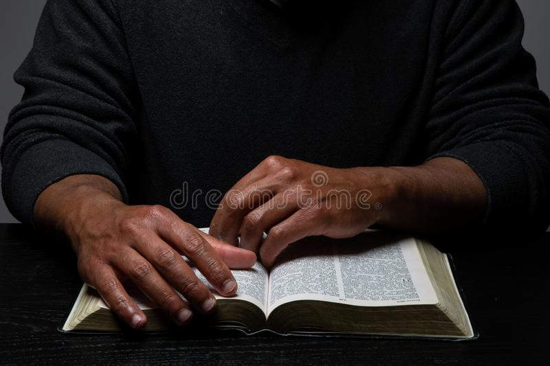 African American Person Studying the Bible Sitting at Desk. On Gray Background royalty free stock images