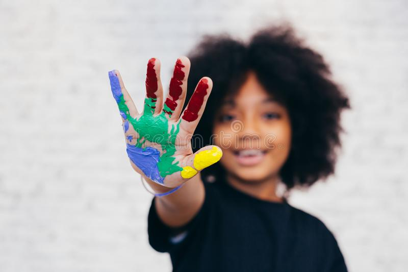 African American playful and creative kid getting hands dirty wi. Th many colors - in white brick background stock photography