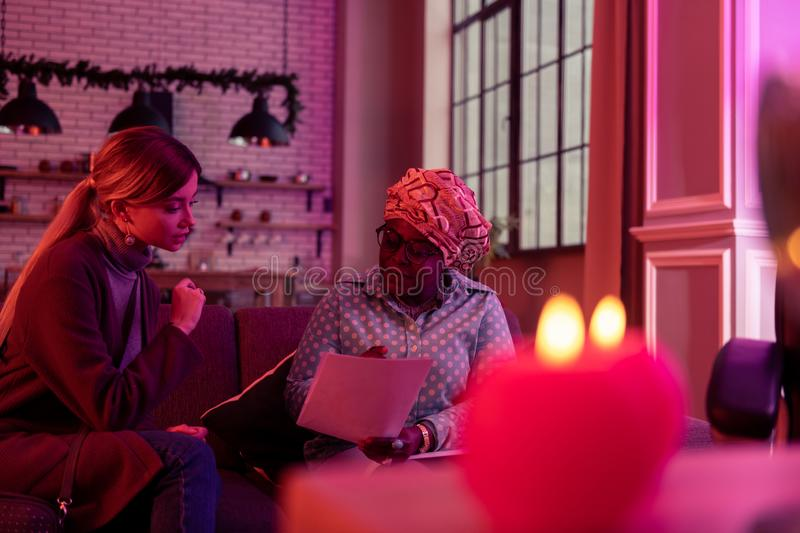 African american plump fortune-teller in ethnic headwear looking concentrated. Important information. African american plump fortune-teller wearing ethnic stock images