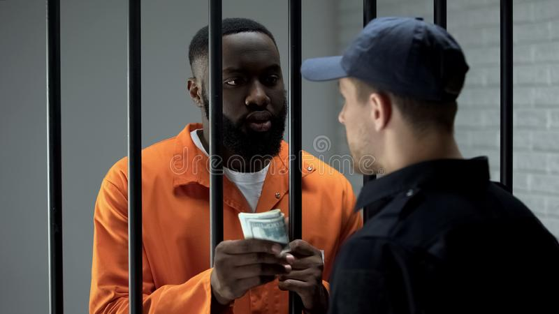 African american prisoner giving dollar cash to guard, corruption in jail, bribe. Stock photo royalty free stock photography