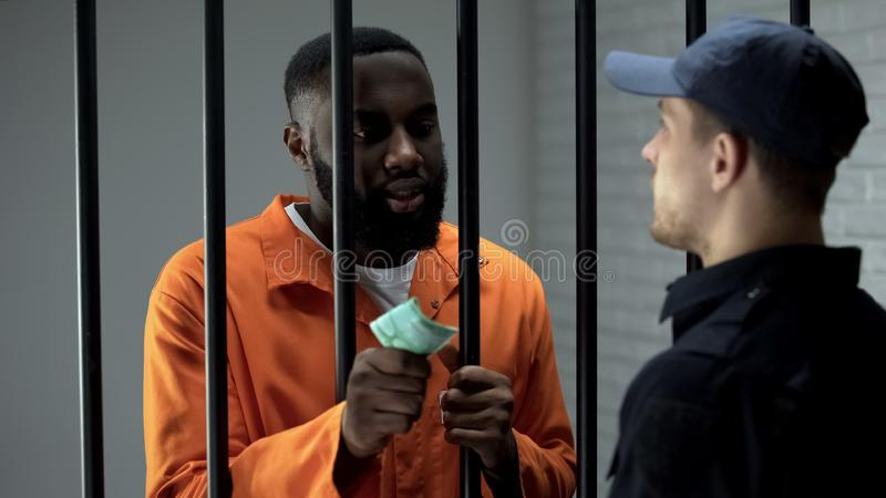 African american prisoner giving euro cash to guard, corruption in jail, bribe. Stock photo royalty free stock photos
