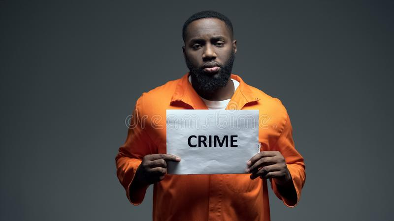 African-american prisoner holding crime sign, looking to camera, awareness stock photo