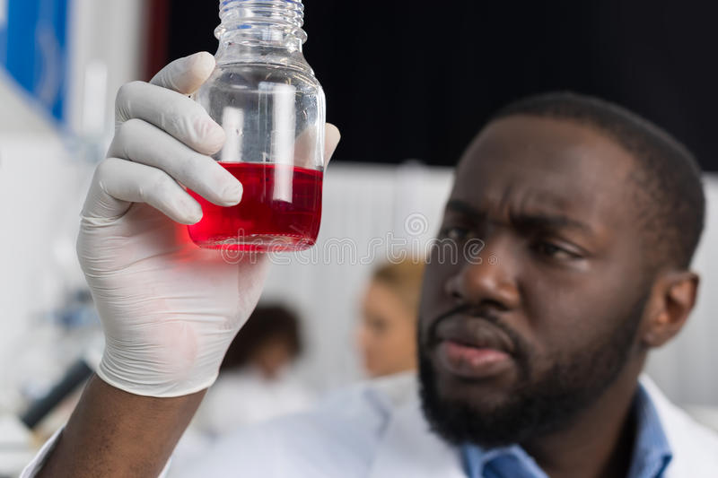 African American Scientist Examine Flask With Red Luquid Working In Modern Laboratory, Male Researcher Making Experiment royalty free stock photo