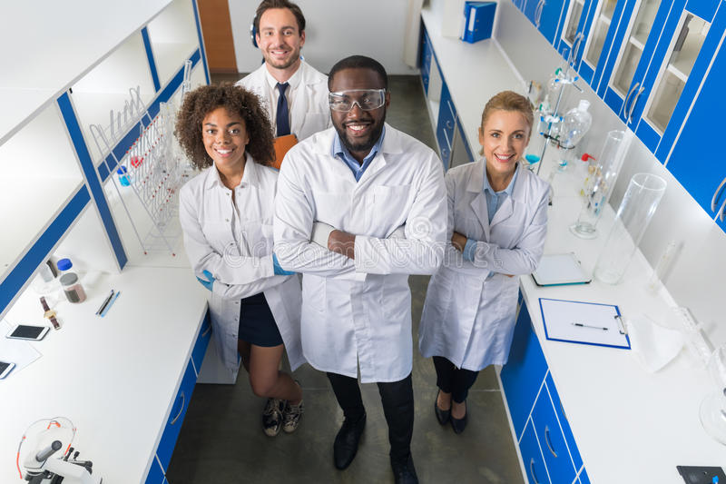 African American Scientist With Group Of Researchers In Modern Laboratory Happy Smiling, Mix Race Team Of Scientific stock photography