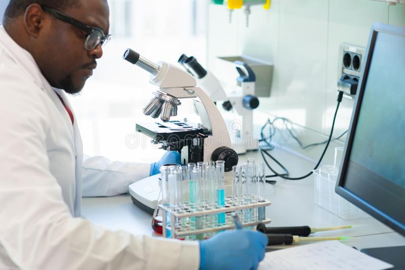 African-american man working in lab. Scientist doctor making medical research. Laboratory tools: microscope, test tubes. African-american scientist working in stock photos