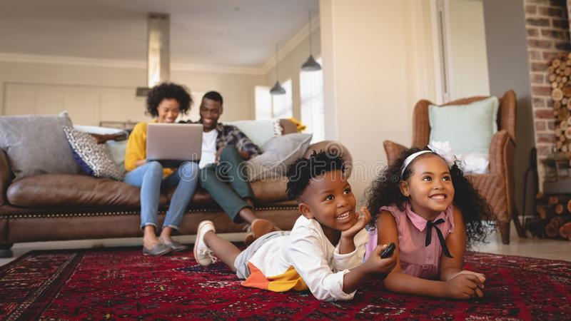 African American sibling lying on floor and watching television while parents using laptop on sofa royalty free stock photography