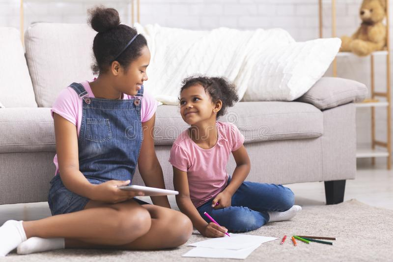 African american sisters drawing with colorful pencils on floor royalty free stock photography
