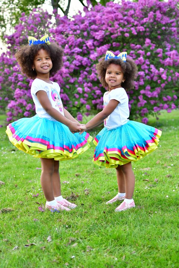 African American sisters are playing in the park curly African American sisters in dance dresses on the grass and bushes of lilac. African American sisters are stock photo