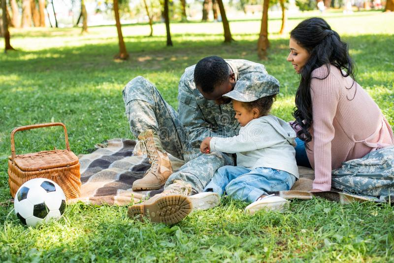 African american soldier in military uniform spending time with family at picnic. In park stock photography