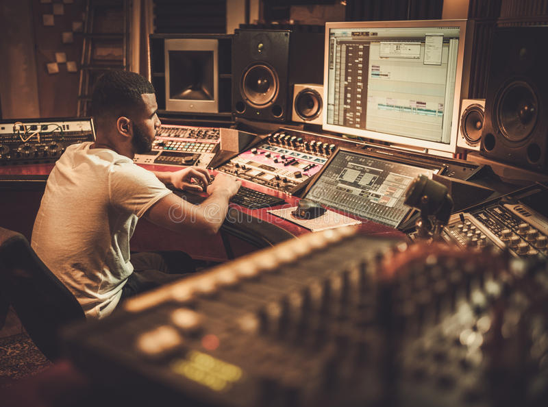 African american sound engineer working at mixing panel in boutique recording studio royalty free stock photography
