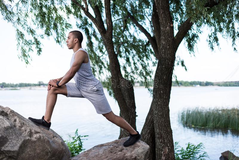 African american sportsman stretching at riverside royalty free stock photography