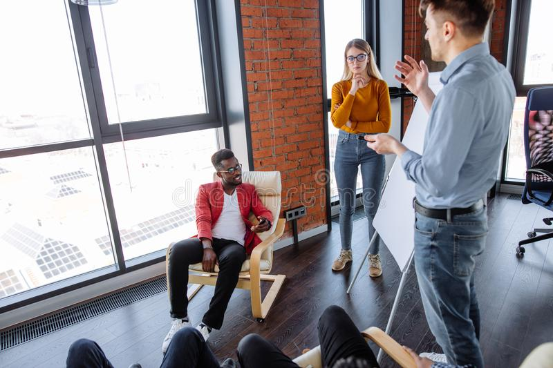 Multi-ethnic people planning business strategy with scheme on flip chart stock photos
