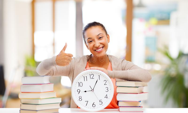 African american student with clock and books royalty free stock photo