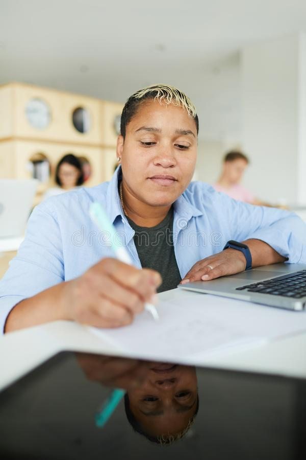African-American student making notes in workbook. Focused young African-American student with fitness tracker sitting at table with device and making notes in stock images