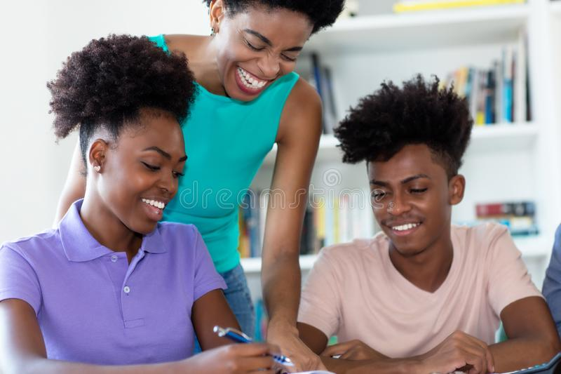 African american students learning with mature female teacher royalty free stock photos