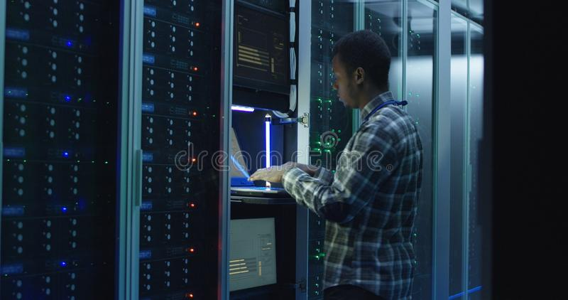 Bearded african American IT specialist setting servers in data center stock photos