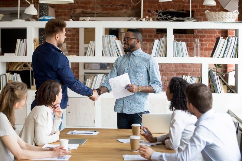 Team leader handshake make employee greeting with success. African American team leader or boss handshake Caucasian employee congratulating with work success stock image