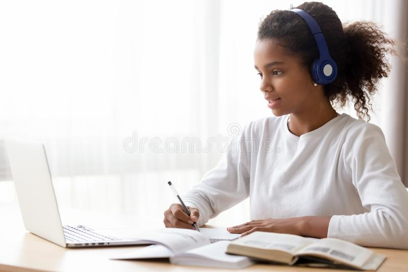 African American teen girl wearing headphones learning language online. Using laptop, looking at screen, doing school tasks at home, writing notes, listening royalty free stock photography