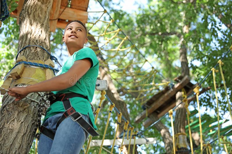 African-American teenage boy climbing. In adventure park. Summer camp royalty free stock images