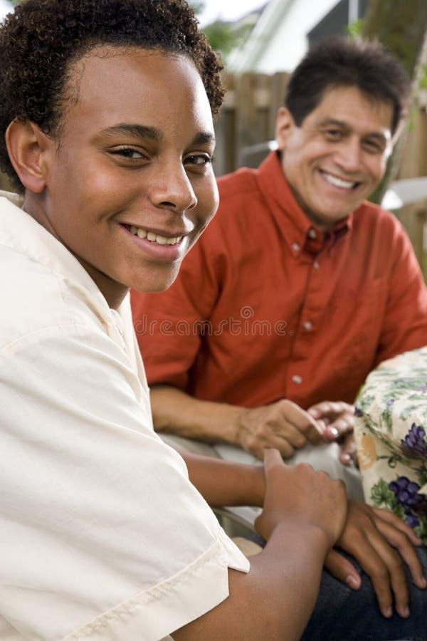 African American teenage boy with Hispanic man stock photo