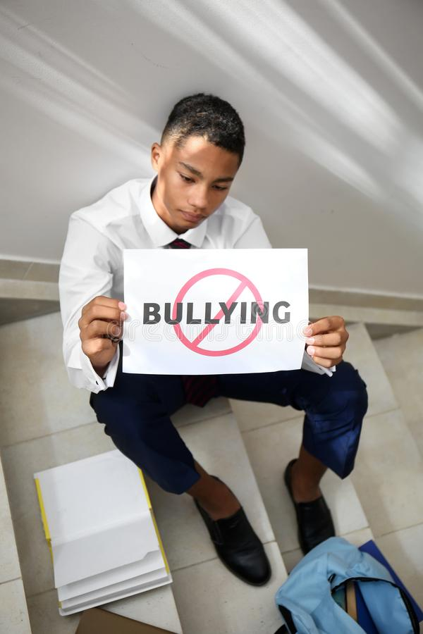 African-American teenage boy holding sheet of paper with word BULLYING at school royalty free stock photo