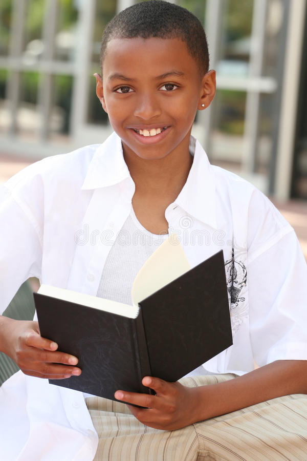 African American Teenager Boy Reading a Book. On a bench outdoors, city street stock photos
