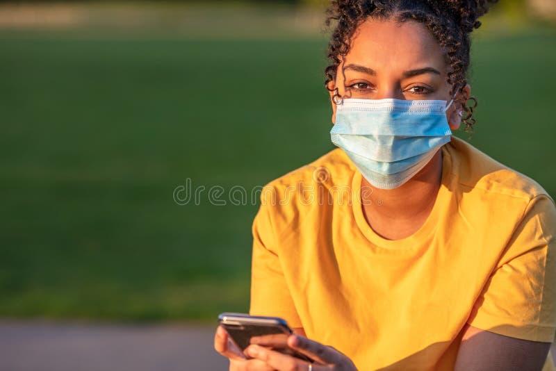 African American Teenager Girl Woman Wearing Coronavirus COVID-19 Face Mask. Mixed race biracial African American teenager teen girl young woman wearing a face royalty free stock photos