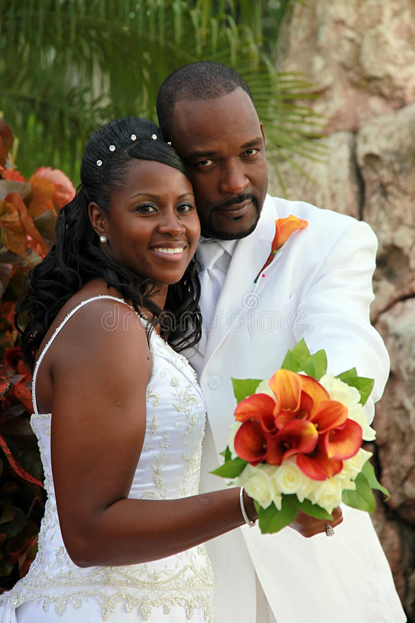 African american wedding couple. Half body portrait of an african american couple holding bouquet of flowers stock photo