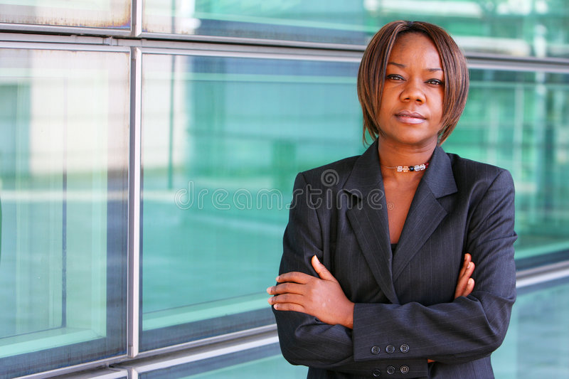 African american woman with arms folded. Confidently outside an office environment royalty free stock image
