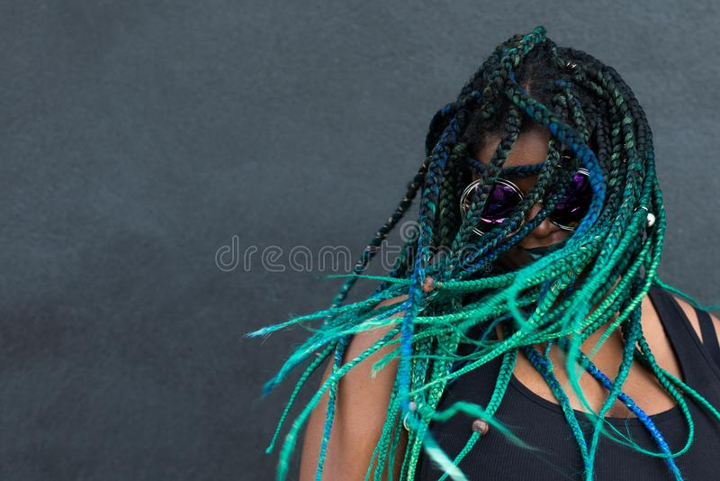 African American Woman with Beautiful Teal Green Blue Braids. In hair tossing hair in action shot on dark background with oversized sunglasses stock photos