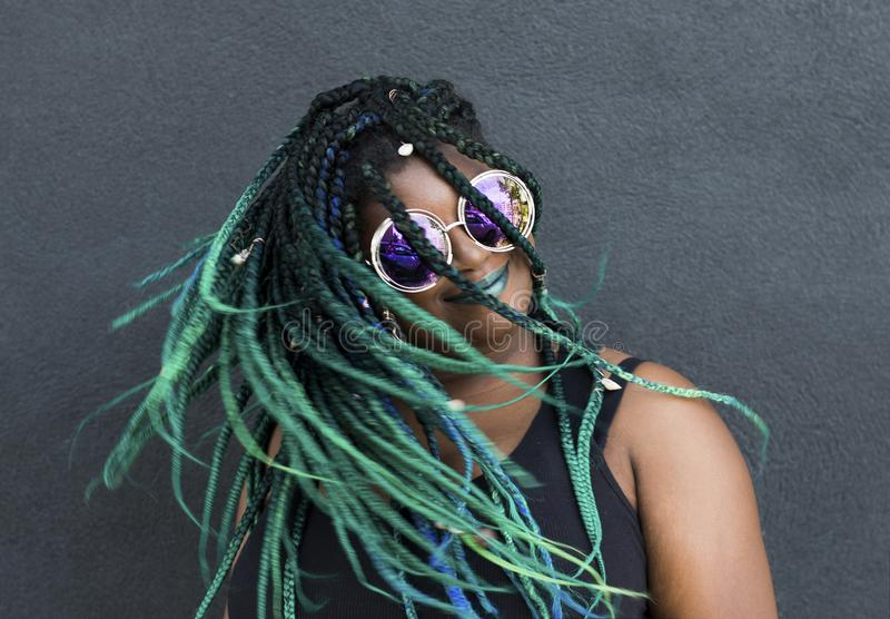 African American Woman with Beautiful Teal Green Blue Braids. In hair tossing hair in action shot on dark background with oversized sunglasses stock photography