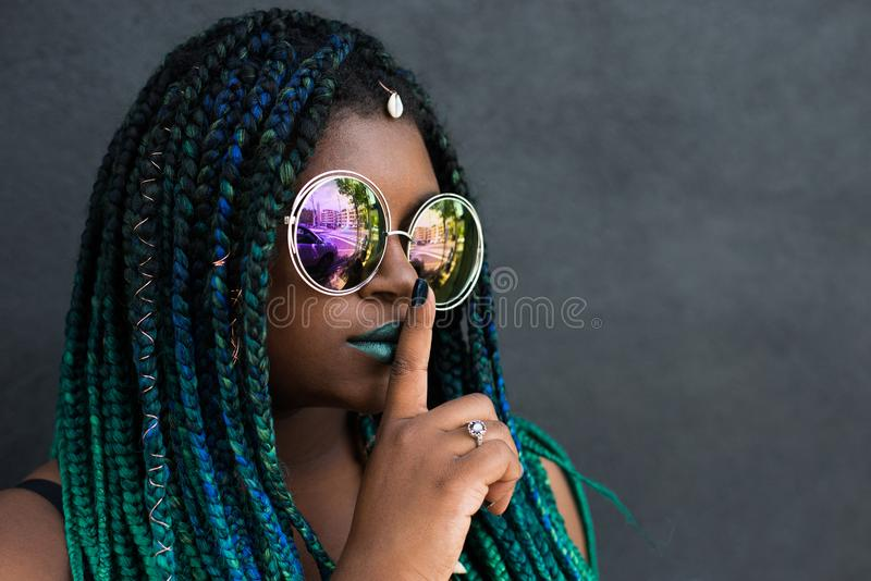 African American Woman with Beautiful Teal Green Blue Braids. In hair shushing with one finger stock images