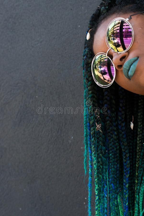 African American Woman with Beautiful Teal Green Blue Braids. In hair close up with giant sunglasses and green lipstick stock photography