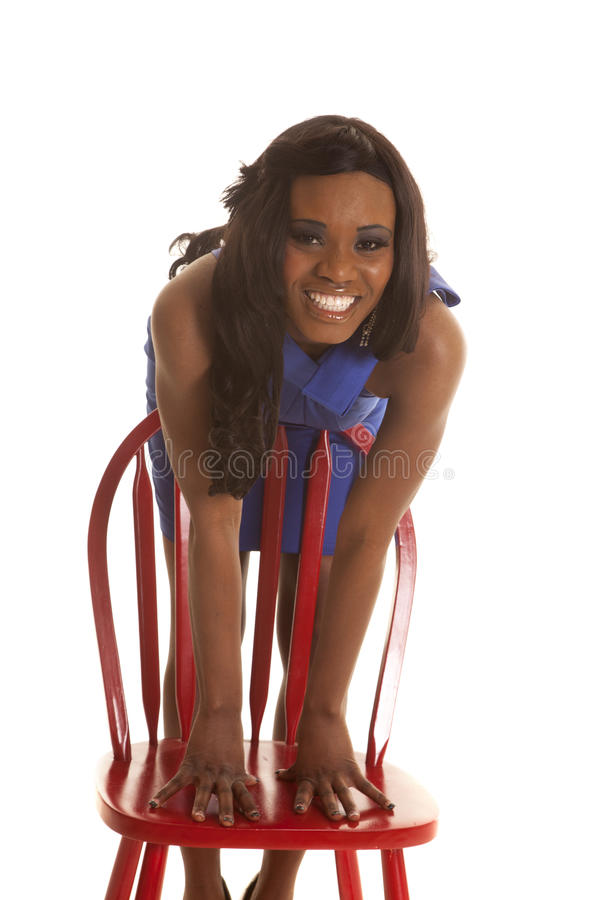 African American Woman Blue Dress Lean On Red Chair Stock