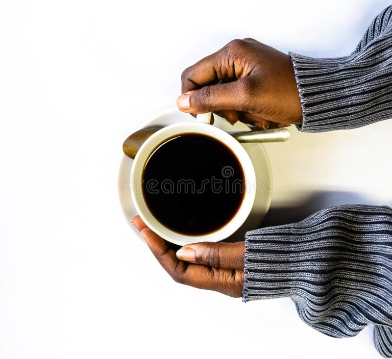 African American woman both hands holding a white cup of coffee. Black Female hands holding a hot cup of coffee with foam stock photo