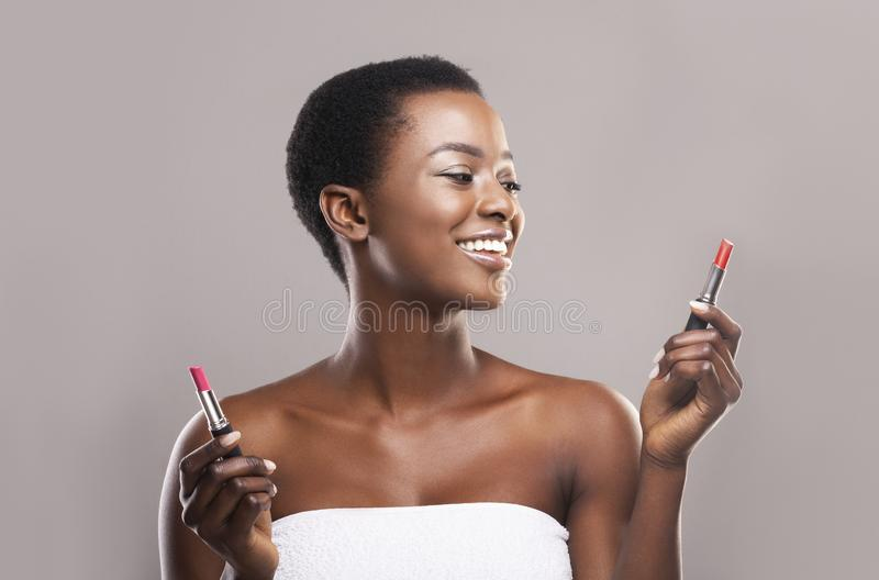 African american woman choosing between two lipstick colors. Difficult choice. African american woman choosing between two lipstick colors, red and pink, over royalty free stock photos