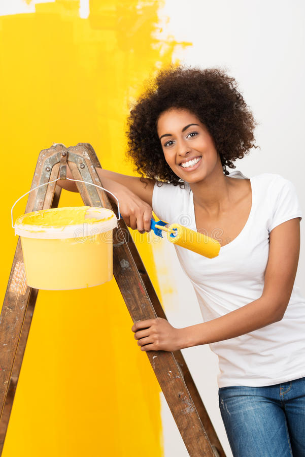 African American woman doing home renovations. Beautiful young African American woman with a lovely smile doing home renovations standing on a wooden stepladder stock photos
