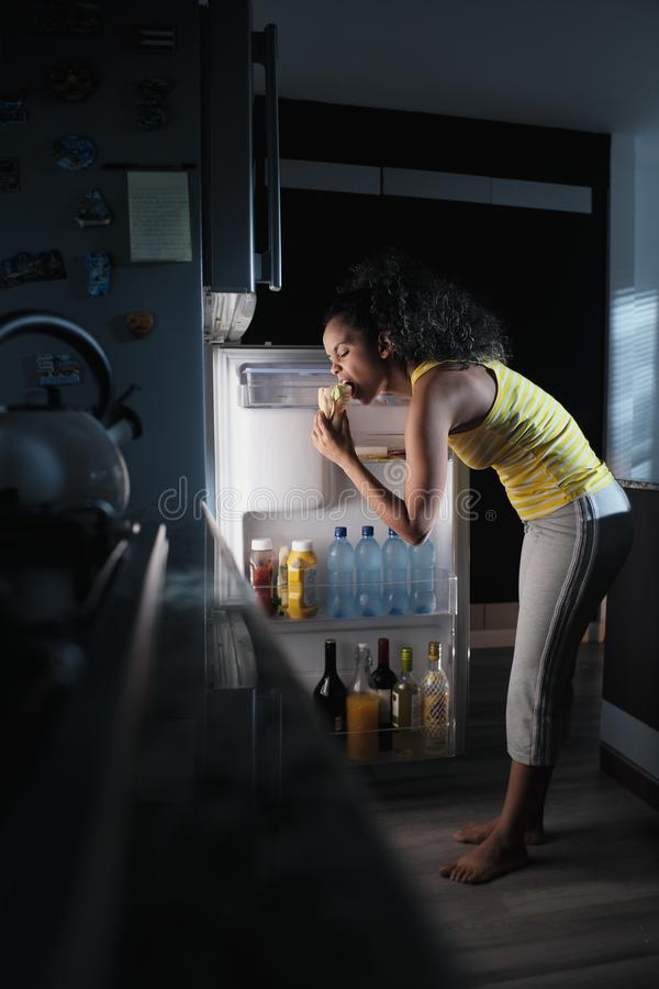 Black Woman Looking into Fridge For Midnight Snack stock image