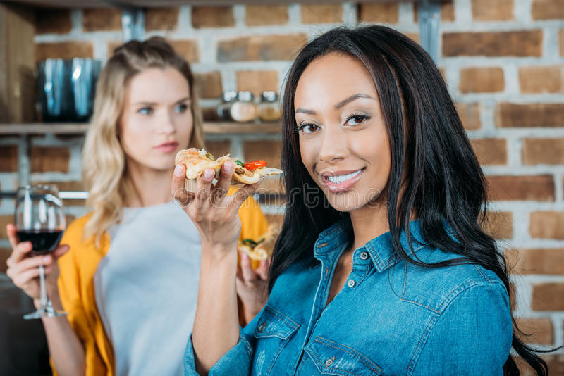 African american woman eating pizza while friend drinking wine behind stock photo
