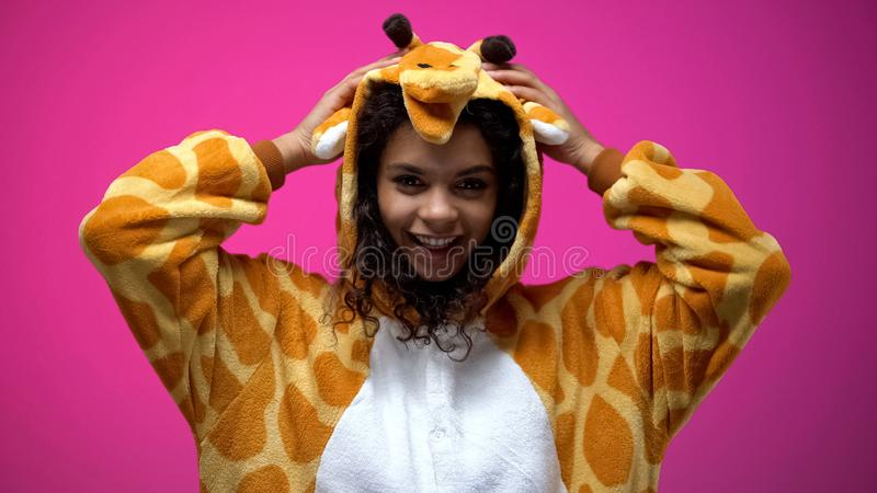 African american woman fooling around wearing funny giraffe pajama, having fun royalty free stock photography