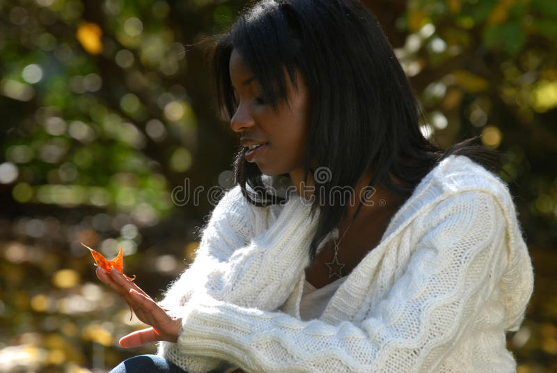 African-American woman gazes at a leaf royalty free stock image