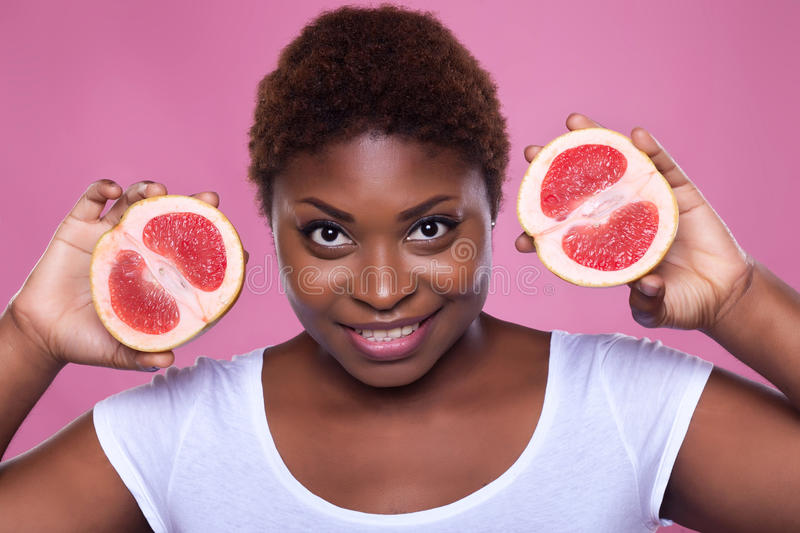 African-American woman with a grapefruit on a pink background, stock image