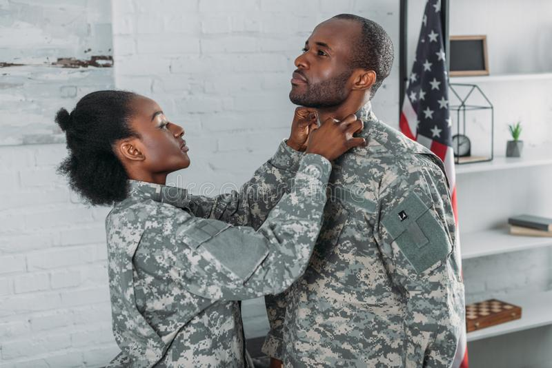 African american woman helping man to get dressed royalty free stock photography